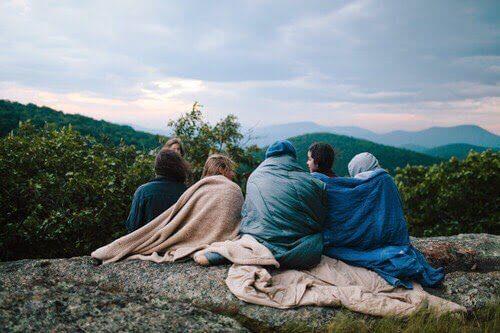 Personer der sidder udenfor med taeppe om sig