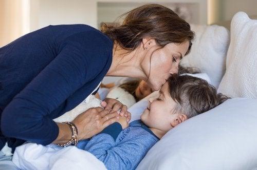 Kvinde der kysser sit barn i sengen