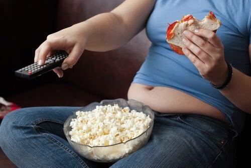Person der sidder foran fjernsynet og spiser sandwich og popkorn