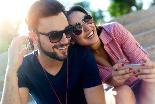 Par der sidder udenfor med en mobil og hoerer musik