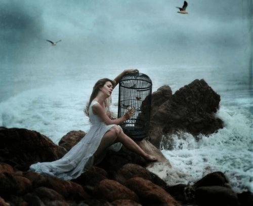Kvinde med et fuglebur ved vandet