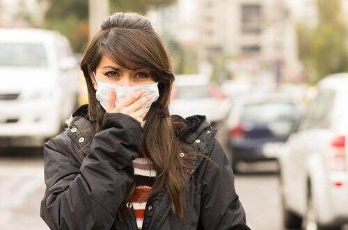 Kvinde der har maske for munden udenfor