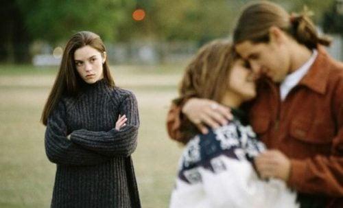 Par der krammer og en ung kvinde der stirrer i baggrunden