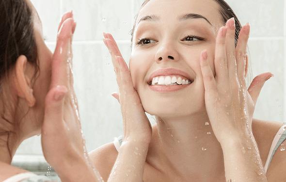 Kvinde der hydrerer sit ansigt