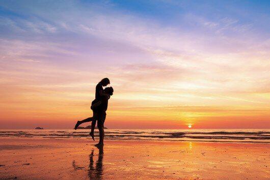 Mand der loefter sin partner op ved solnedgang