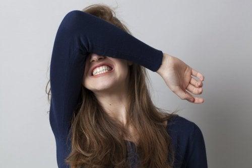 Kvinde med arm foran oejnene der skaerer taender