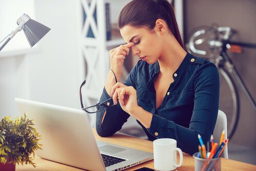 Kvinde med stress foran computeren