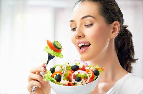 Kvinde der spiser salat - tid til at traene
