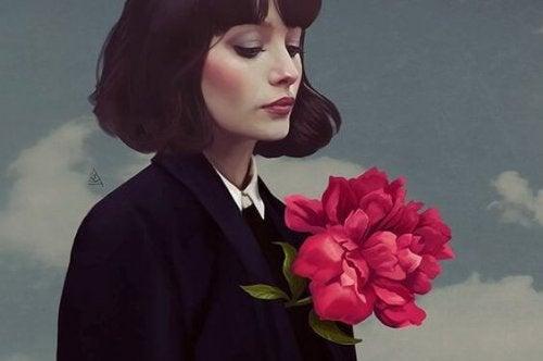 Kvinde der kigger ned paa en blomst