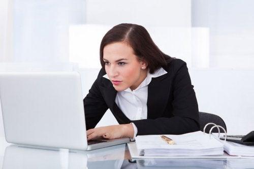 Kvinde der sidder foroverboejet ved computeren
