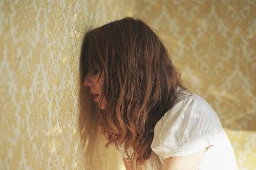 Kvinde med hovedet mod muren