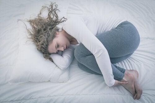 Kvinde der ligger i fosterstilling i sengen