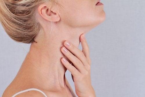 Kvinde der tager sig til halsen
