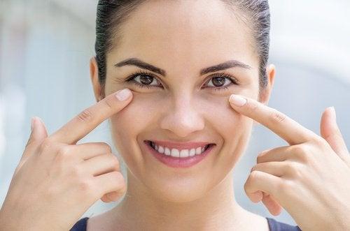 Kvinde der smiler mens hun har en finger under oejnene