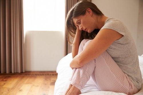 Kvinde sidder i seng deprimeret