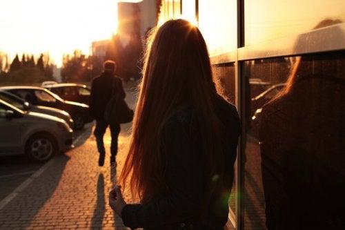 Ung kvinde der staar udenfor og kigger mod solen