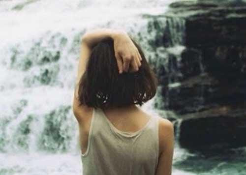 Pige der staar foran et vandfald
