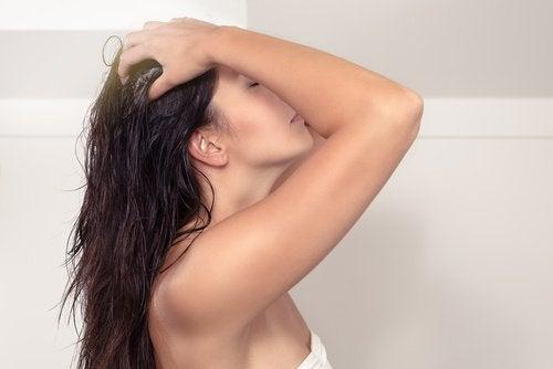 Kvinde der foerer fingrene gennem haaret
