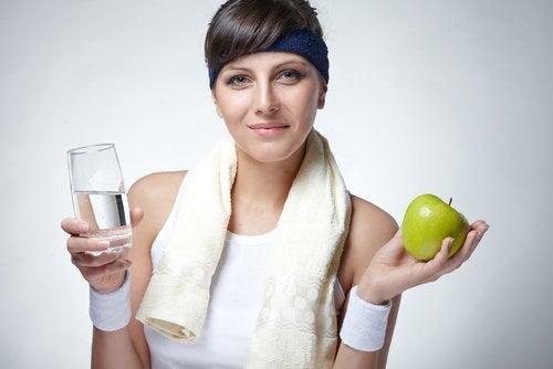 Kvinde der holder et glas vand og et aeble