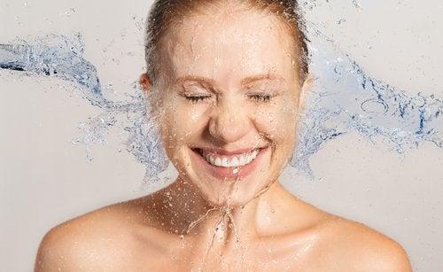 Kvinde der smiler med vand i ansigtet