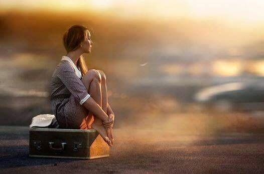 Ung kvinde der sidder paa en kuffert udenfor