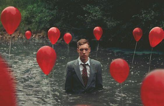 Man i jakkesaet i en flod omgivet af roede balloner