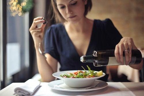 Kvinde der haelder olie paa sin salat