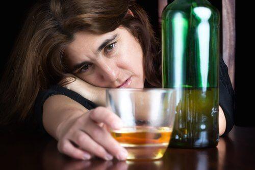 Kvinde der haenger over et glas alkohol