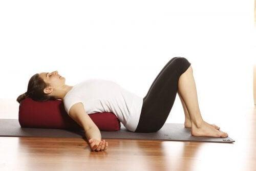 Kvinde der ligger paa en yoga maatte