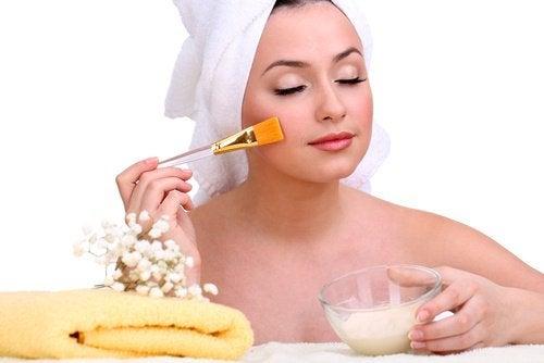 Kvinde der paafoerer olie paa sin hud