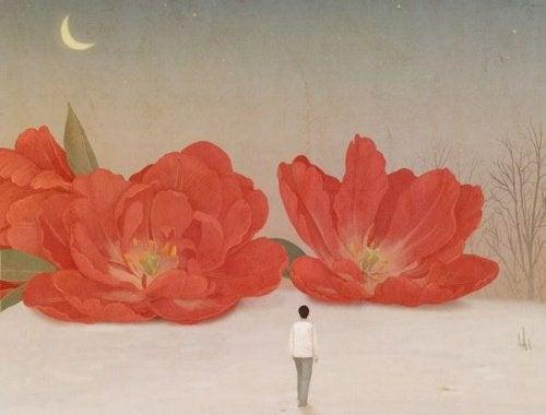 Person der staar foran nogle store blomster