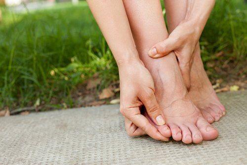Person der har haender nede omkring foden
