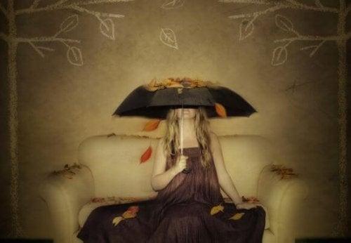 Kvinde der sidder under en paraply