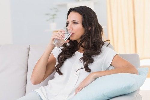 Kvinde der drikker vand i sofaen