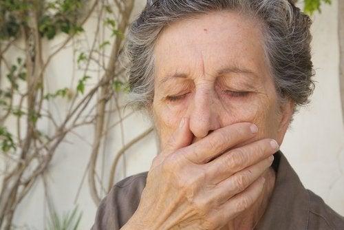 Aeldre kvinde der holder sig for munden