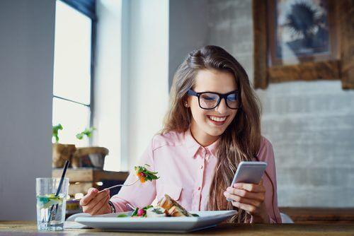 Kvinde der sidder med sin mobil mens hun spiser