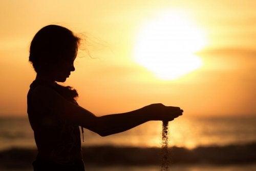 Pige der er ved stranden ved solnedgang