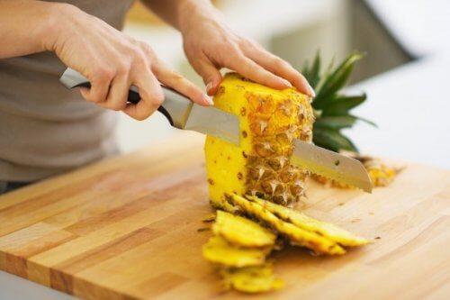 Person skærer ananas ud.