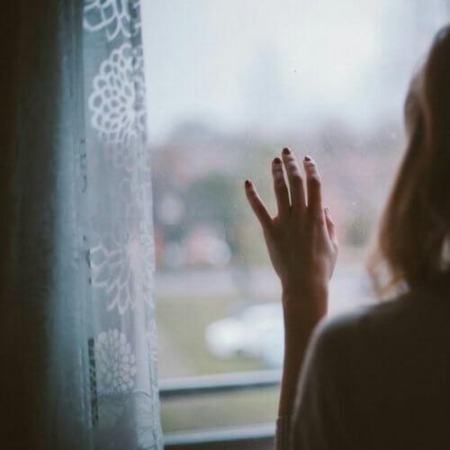 Kvinde der ser ud af et vindue