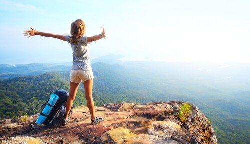 Kvinde der staar paa toppen af en klippe