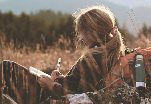 Kvinde der sidder udenfor paa en eng og skriver