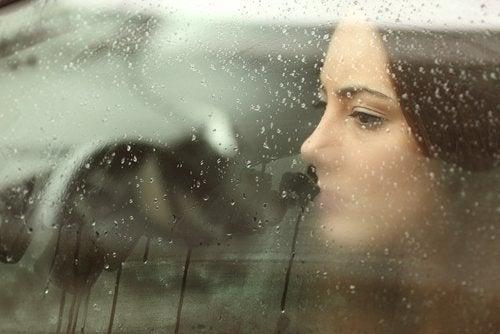 Kvinde der kigger ud gennem en bilrude
