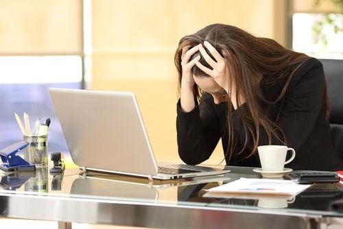 Kvinde på kontor tager sig til hovedet, fordi hun ikke kan overvinde stress