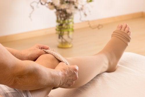 Person der tager stoettebind paa benet