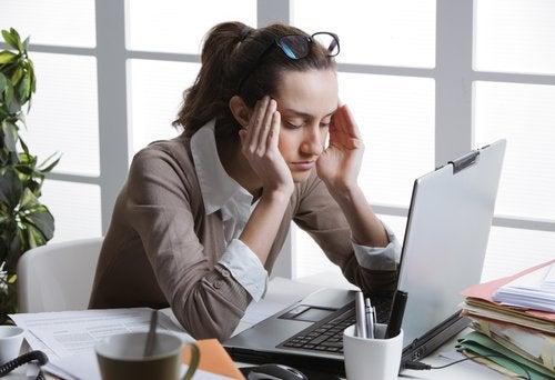 Kvinde der sidder med haenderne paa hovedet foran comupteren