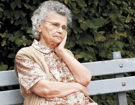 Aeldre kvinde der sidder paa en baenk