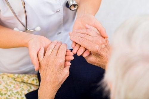 Aeldre kvinde holder laege i haenderne