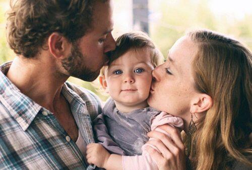 Forældre kysser barn