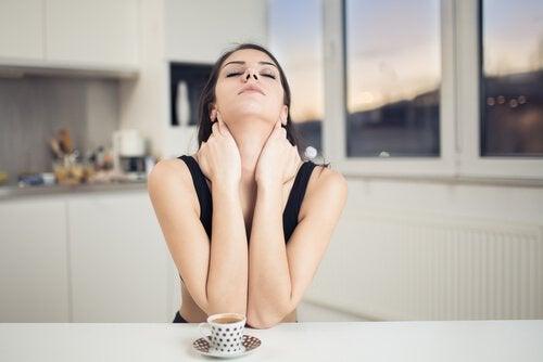 Kvinde der sidder og tager sig til nakken