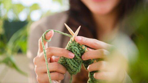 Kvinde strikker med groent garn.
